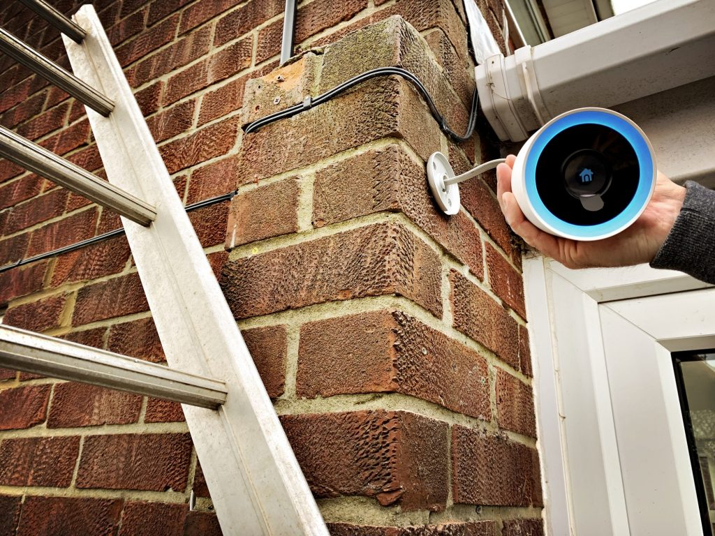 Close up view of a homeowner installing a Google Nest CCTV home security camera over the front door