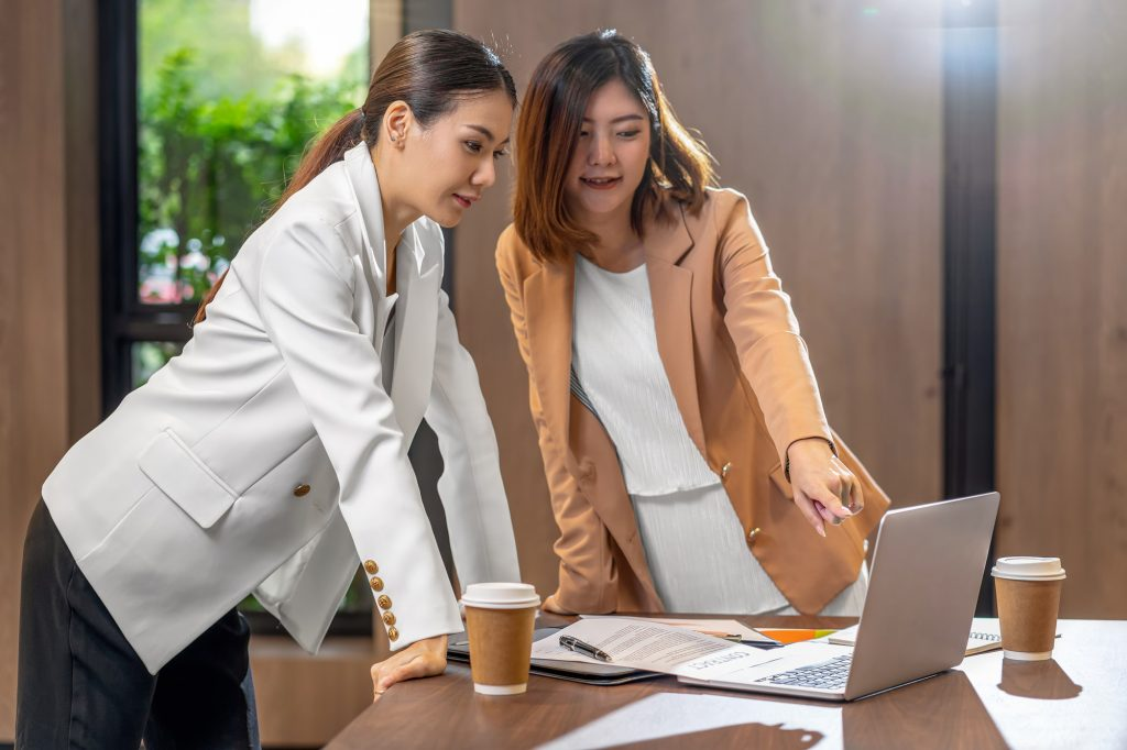 Two asian businesswomen working with the partner business via technology laptop